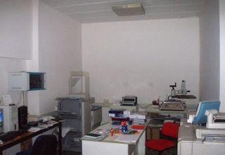 una scrivania,una sedia rossa e delle stampanti