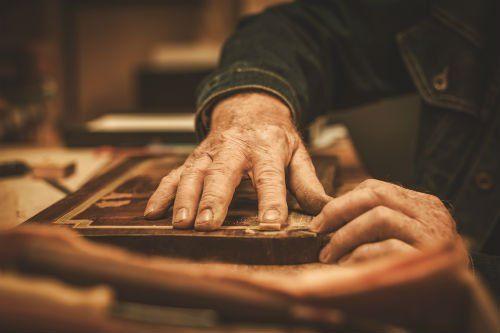 due mani appoggiate su un oggetto di legno d'antiquariato
