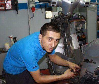 un operaio aggiusta le parti elettriche di uno scooter