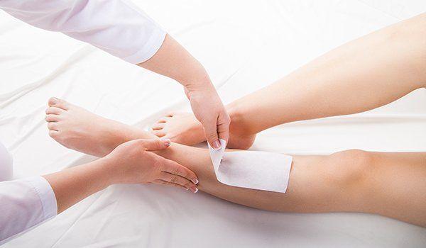 un'estetista mentre depila le gambe a una donna con una striscia di cera