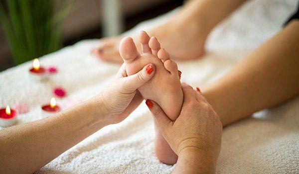 una massaggiatrice mentre massaggia il piede di una donna