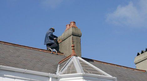 A man on a roof, repairing a chimney