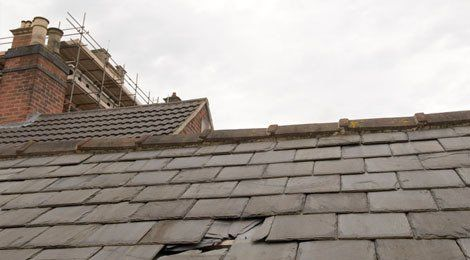 Roof with damaged slates, and scaffolding behind the chimney