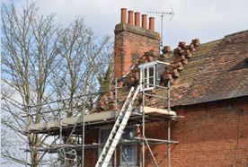 Scaffolding and a ladder against a house with damaged roof and chimney