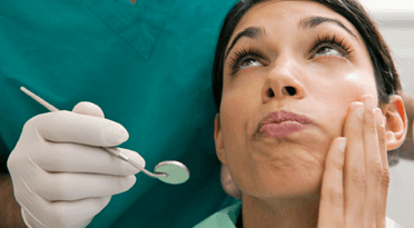 A woman holding her cheek and looking up at a dentist