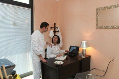 un dentista che parla con una collega seduta alla scrivania