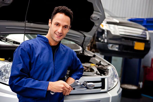Mechanic standing in front of vehicle with tools
