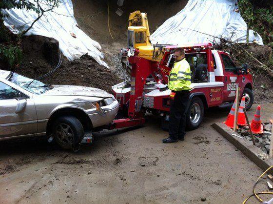 Towtruck driver servicing a damaged car