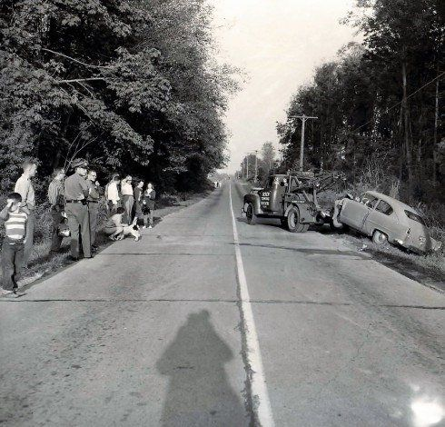 50's era image of a towtruck pulling a car out of a ditch