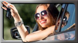 donna sorridente mostra chiavi dell'auto dall'interno dell'abitacolo