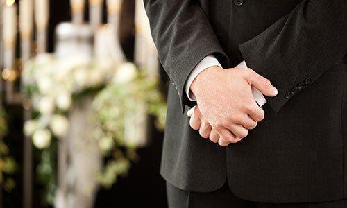 Uomo elegante tiene le mani giunte e fiori bianchi in secondo piano
