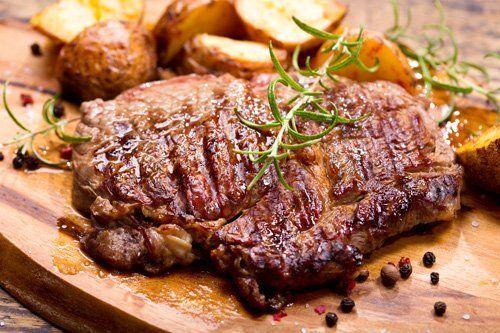 carne alla griglia sul tagliere condita con prezzemolo e pepe nero