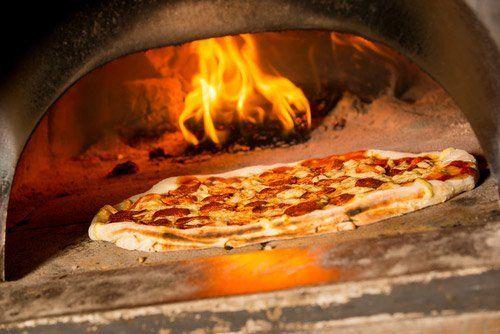 pizza in cottura in forno a legna