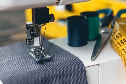 un ago di una macchina da cucire che tiene ferma una stoffa nera e accanto dei fili arrotolati,una forbice e un metro di gomma