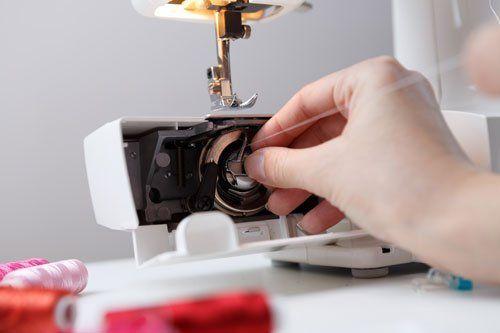 una mano che inserisce un filo dentro a una macchina da cucire