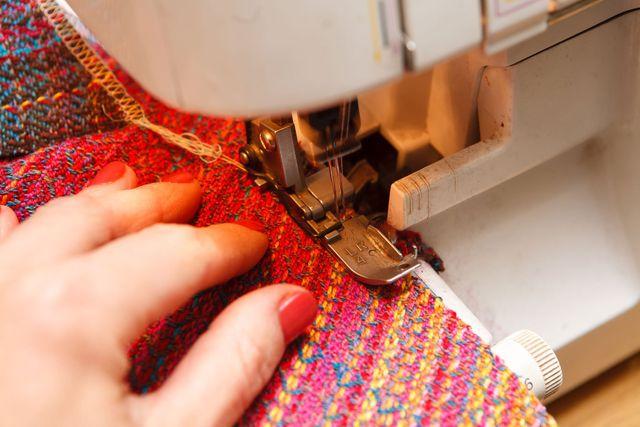 una mano che tiene ferma una stoffa rosa e gialla vicino a una mcchina da cucire