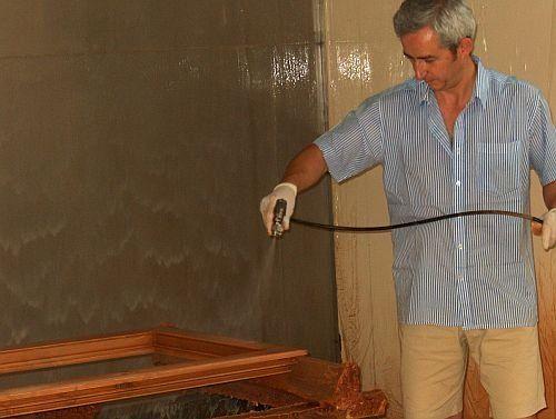 un uomo che con una canna spruzza del liquido su dei telai in legno