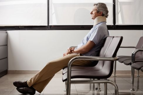 man sitting in a chair wearing a neckbrace