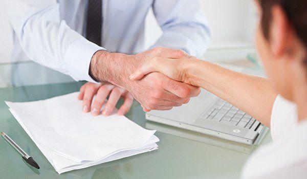 una stretta di mano tra un uomo e una donna seduti alla scrivania