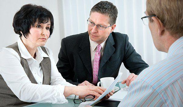 una donna di mezza eta con capelli neri che indossa una camicia bianca e un gilet beige scuro sta parlando seduta a una scrivania con due uomini
