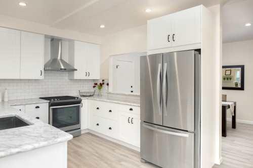 la cucina con mobili bianchi con top in marmo e un frigo
