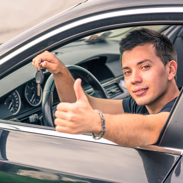 A young man sticking up his thumb as he holds the keys to his new car