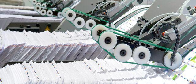 un macchinario per stampe grafiche con delle cinghie e dei rulli e sotto tanti fogli stampati