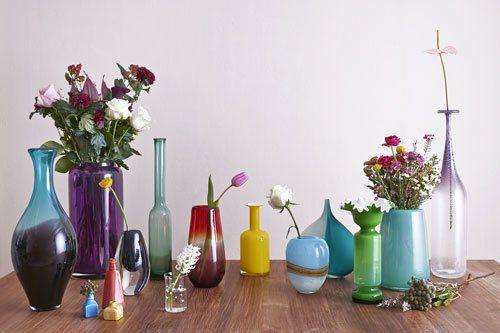 dei vasi di vetro colorati con dei fiori