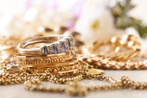 dei braccialetti dorati e un anello d'argento con una pietra blu