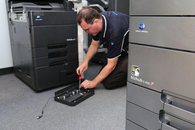 office everything employee fixing photocopier