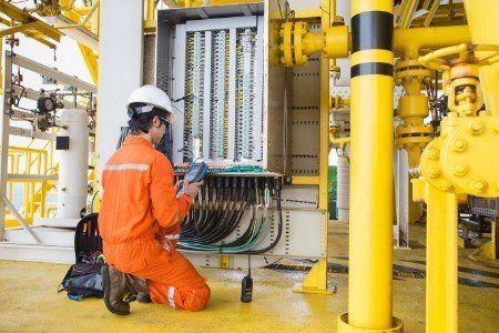 Operaio davanti a una centrale elettrica all'interno di una fabbrica