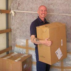 A removal man holding a box and smiling at the camera
