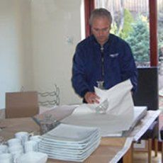A removal man wrapping plates and crockery