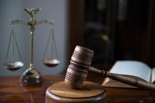 Martello della giustizia, bilancia della giustizia e un  libro aperto