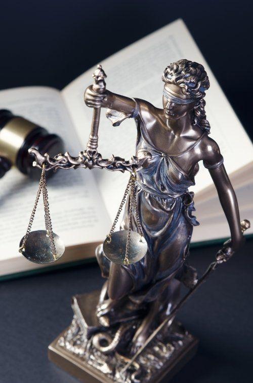 Primo piano della bilancia della giustizia, un martello sul libro aperto
