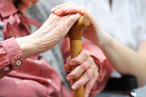 una mano di una donna giovane appoggiata su quella di un'anziana con un bastone