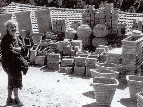immagine in bianco e nero di una signor anziana sorridente e dietro tanti vasi in terracotta