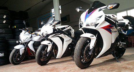 3 moto di color bianco e accanto delle gomme disposte una sopra l'altra