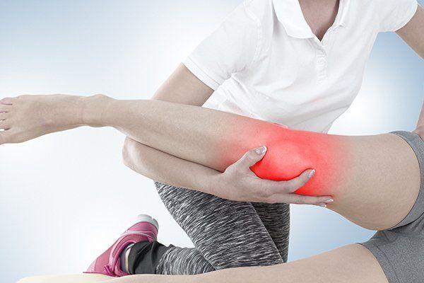 una fisioterapista che sorregge una gamba di una donna con il ginocchio infiammato
