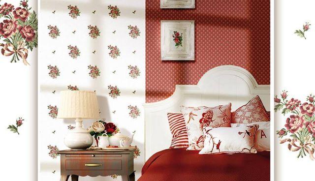 una camera da letto arredata con carta da parati bianca e rossa a disegni