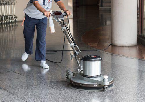 Un impiegato lucida un pavimento con la macchina apposita