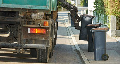 Garbage collector truck collecting the waste and trash bin