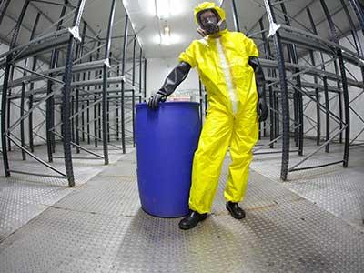 Operaio con barile di rifiuti pericolosi