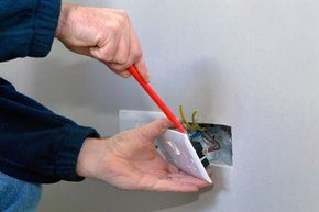 electrician fixing a plug socket