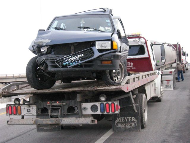 Flatbed towing a wrecked suv