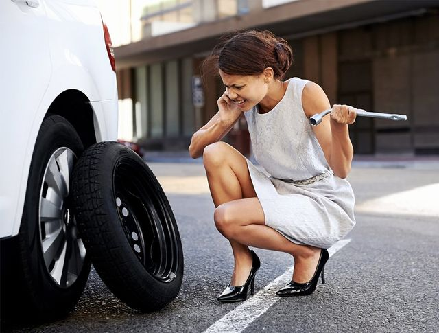 Lady on her cell phone calling for help to change a flat tire