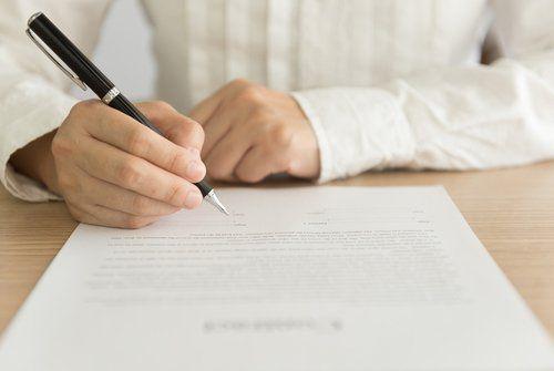 uomo in camicia che firma un documento