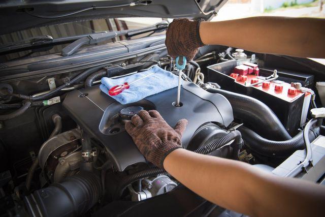 una mano appoggiata sul motore di una macchina