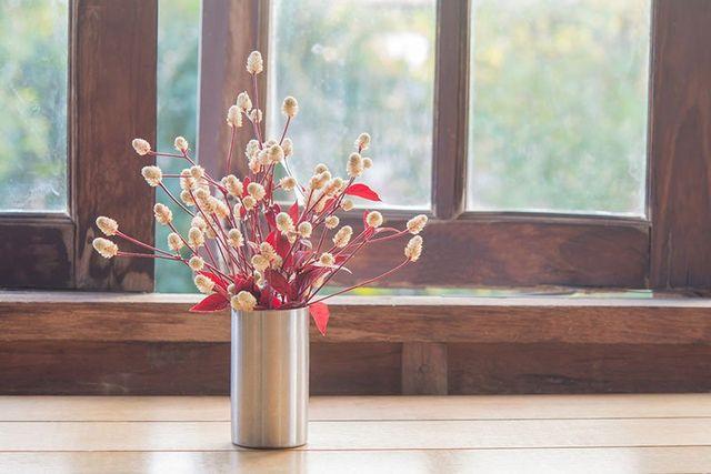 Finestra di legno e vaso di acciaio con fiori secchi