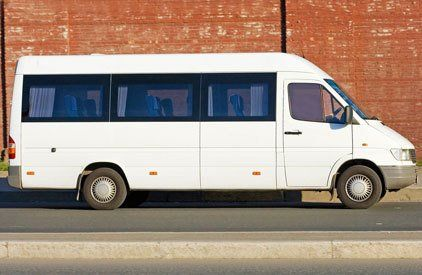 A white minibus in front of a red brick wall